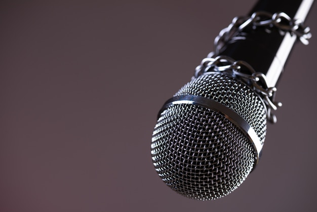 Microphone with a chain, idea of freedom of the press concept.
