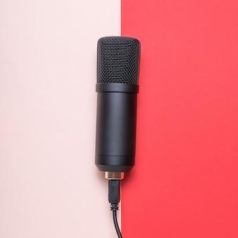 Микрофон с подключенным проводом на красной и розовой поверхности