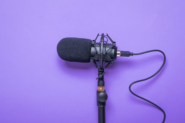 Microphone with a cord screwed to the stand on a purple surface