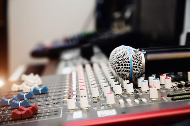 メディアをライブするためのスタジオの職場でのサウンドミキサー付きマイク。