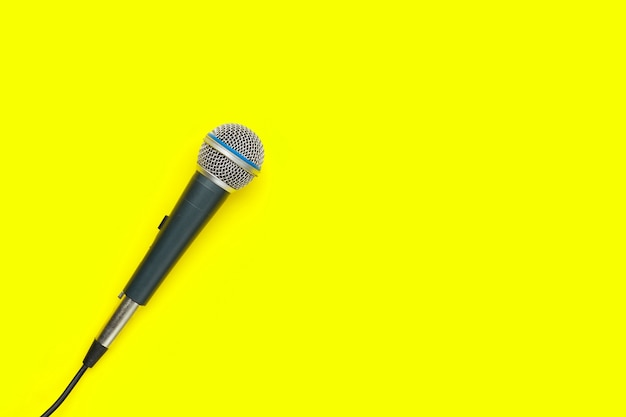 Microphone on yellow background. top view