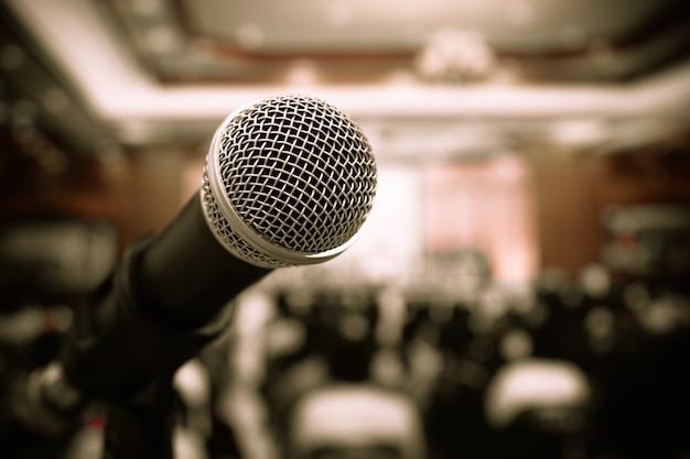 Microphones on abstract blurred of speech in meeting room, front speaking blur people