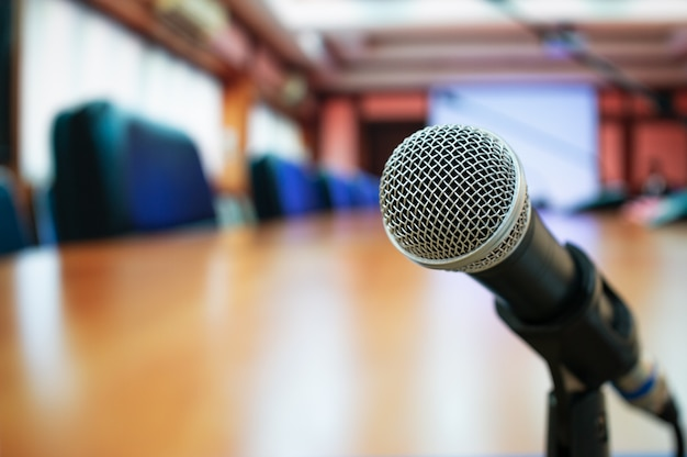 Microphones on abstract blurred of speech in seminar room or front speaking conference hall light