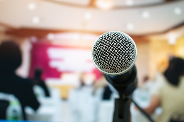 Microphones on abstract blurred of speech in seminar room or front speaking conference