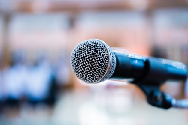 Microphones on abstract blurred of speech in seminar room, speaking conference hall