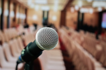 Microphones on abstract blurred of speech in seminar room or front speaking conference hal