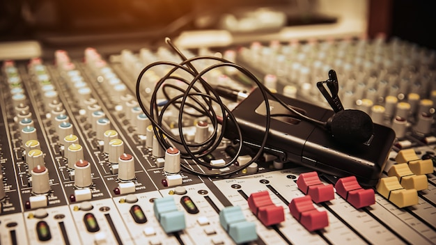 スタジオの職場でのオーディオミキサー付きマイク。