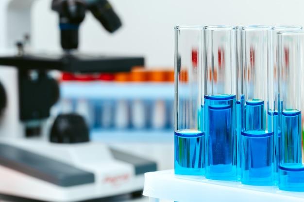 顕微鏡と実験室のテーブルの試験管をクローズアップ