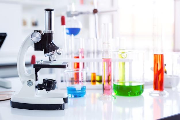 Микроскоп и пробирки с лабораторной посудой в лаборатории, исследования и научная концепция