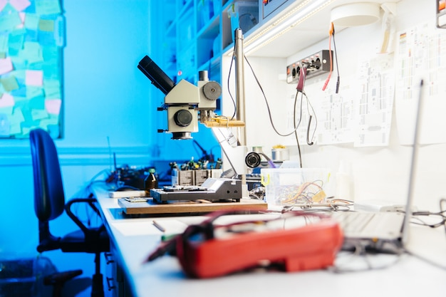 Microscope on desk in scientific laboratory workshop with blue and white color scheme