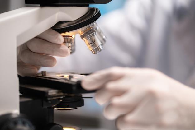Микроскоп в медицинской исследовательской лаборатории или научной лаборатории, исследование для создания вакцины для защиты от коронавируса covid-19