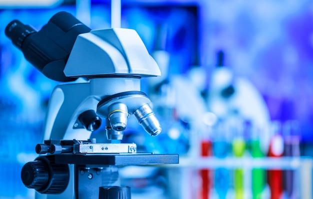 実験室の青色光で化学試験管装置を備えた顕微鏡と実験室、コピースペースを備えた科学と実験の概念。