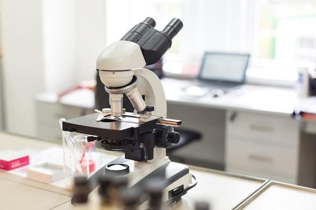 Микроскоп в лаборатории на фоне стола с компьютером