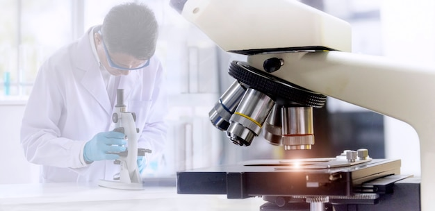 Microscope with blurred background of scientist researching by microscopy technique in laboratory.