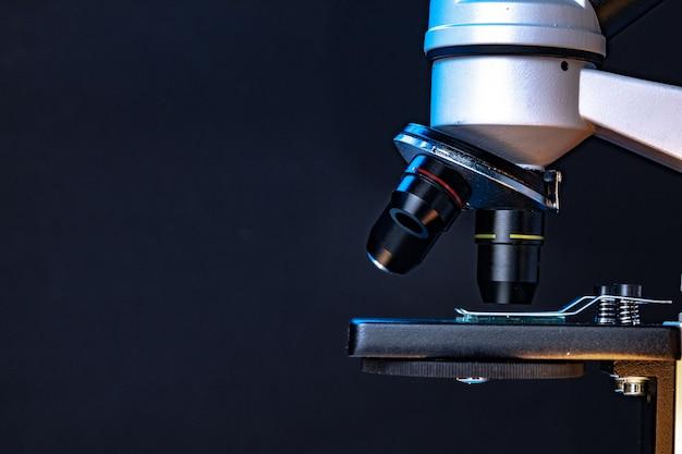 暗い背景に対してレンズ付き顕微鏡をクローズアップ