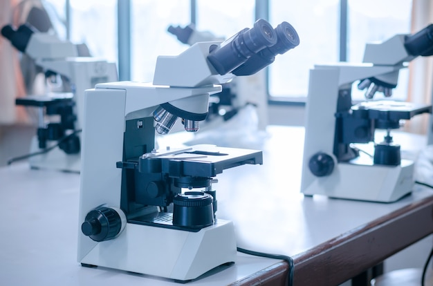 Microscope with micro plate on white table in laboratory setting for research and learning