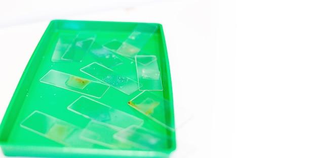 Микроскопия и использованные лабораторные очки для микроскопа лежат на зеленом подносе после результата исследования
