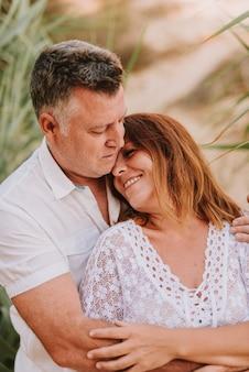일몰 동안 해변의 모래 언덕에 흰색 드레스를 입고 중반 성인 커플 포옹과 키스