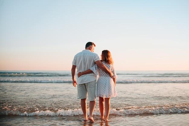 중반 성인 커플 포옹과 키스, 일몰 동안 해변에서 흰색 드레스를 입고