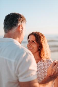 일몰 동안 해변에서 흰색 드레스를 입고 서로 눈을 찾고 중반 성인 부부