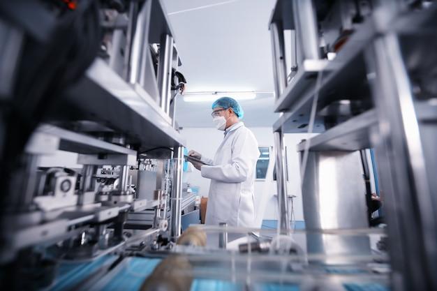 工場の生産ラインで機械部品を検査する中年男性エンジニア。