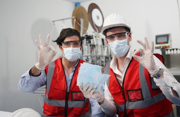 Инженеры-мужчины среднего возраста изучают детали машины на производственной линии медицинских масок на фабрике.