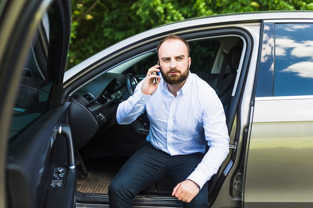 Mid adult man sitting in a car with open door talking on smartphone
