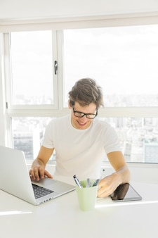 Mid adult man wearing spectacles using laptop in front of glass window