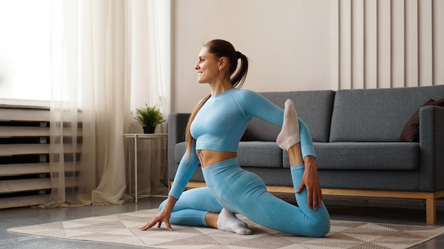 Mid adult woman training at home. horizontal shape, full length, side view. happy woman doing fitness and yoga at home.