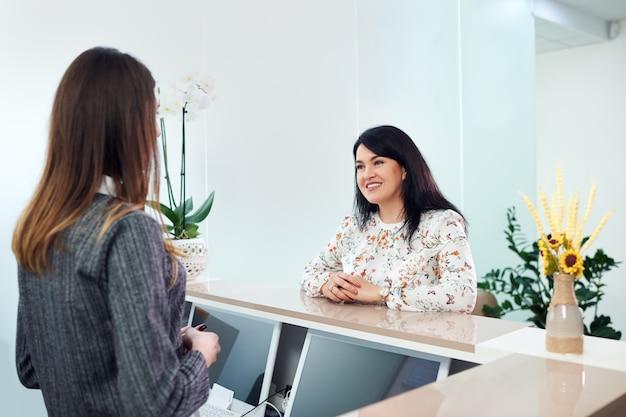 Середина взрослая женщина с красивой улыбкой разговаривает с молодой женщиной портье