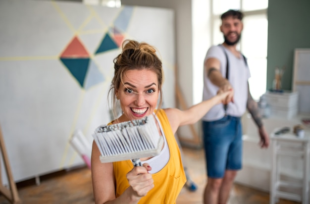 Mid adults couple having fun when painting wall indoors at home, relocation and diy concept.