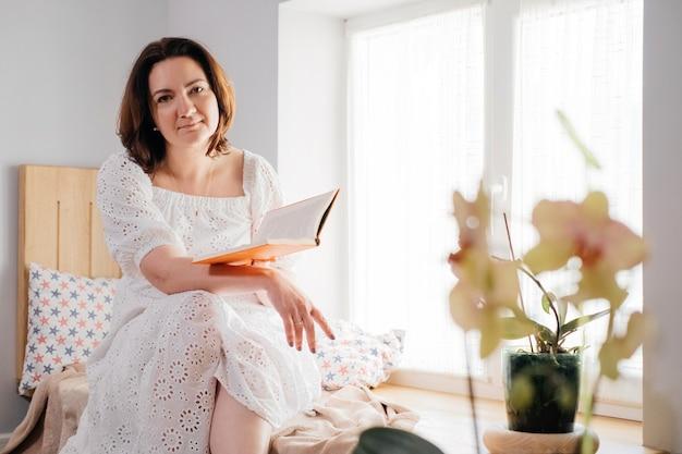 窓際で本を読んでいる中年の大人の女性 Premium写真