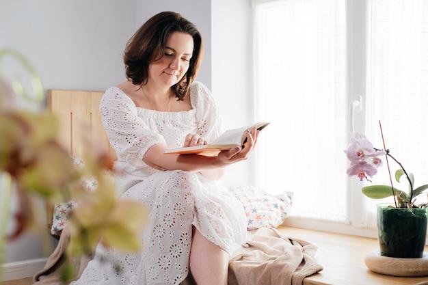 窓際で本を読んでいる中年の大人の女性