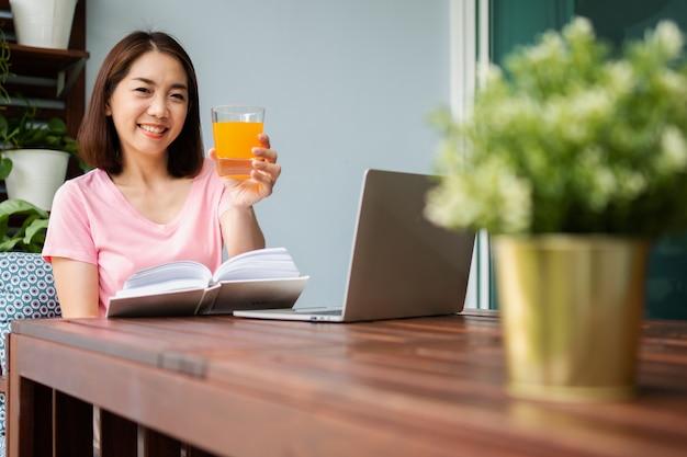 중년의 아시아 여성이 집에서 책을 읽고 오렌지 주스 잔을 들고 있습니다. 건강 관리 및 건강을 위한 식사의 개념