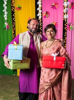 装飾的な背景に立っている間ディワリ祭のギフトボックスを保持している中年のインドのカップル