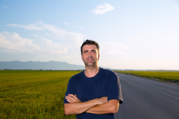Mid age man in road at meadows posing crossed arms