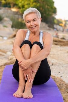 중간 나이 여자 요가 매트에 앉아 해변에서 웃고. 세로 세로