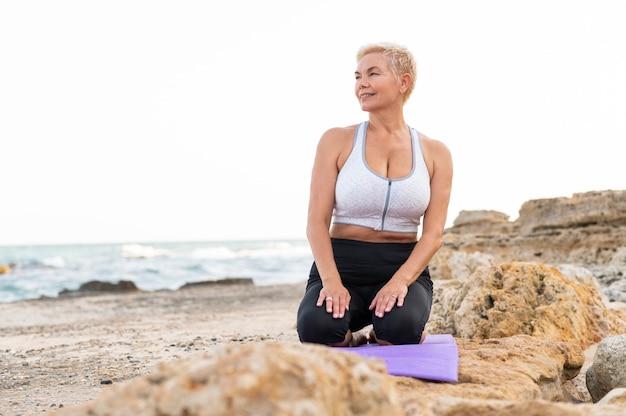 海沿いの中年スポーティーな女性がピラティスのエクササイズをします。高品質の写真