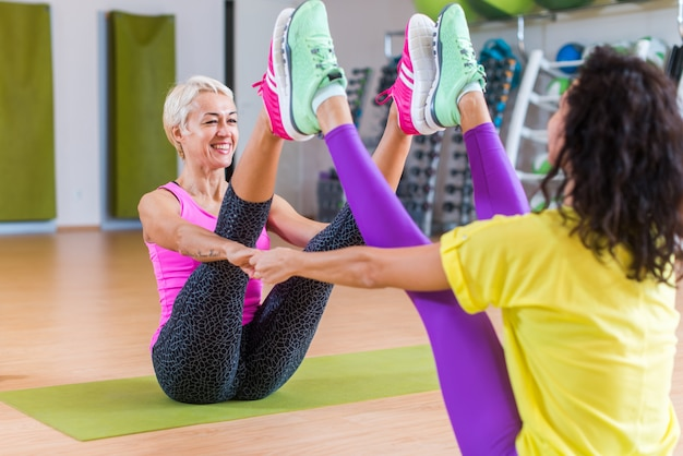 Mid-aged woman working out in pairs on mats in a gym.
