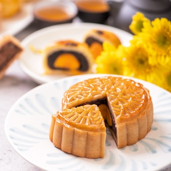 Mid-autumn festival traditional food concept - beautiful cut moon cake on blue pattern plate on white background with flower, close up, copy space
