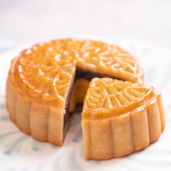 중추절 전통 음식 개념-꽃과 흰색 배경에 파란색 패턴 접시에 아름 다운 컷된 달 케이크, 가까이, 복사 공간