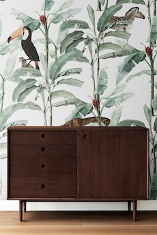 Mid century modern wood cabinet by a leafty wall
