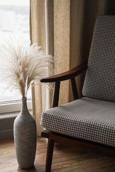 Стул в стиле ретро середины века и букет пампасных трав в глиняном горшке на фоне окна с занавесками