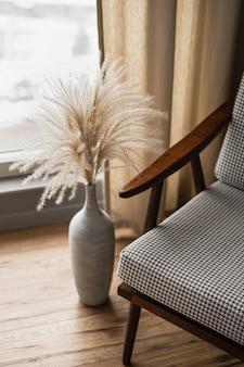 カーテンが付いている窓に対して土鍋のミッドセンチュリーのレトロな椅子およびパンパス草の花束