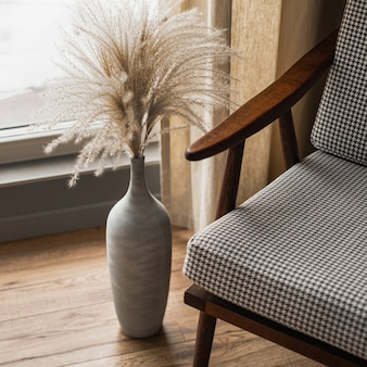 Mid-century retro chair and pampas grass bouquet in clay pot against window with curtains