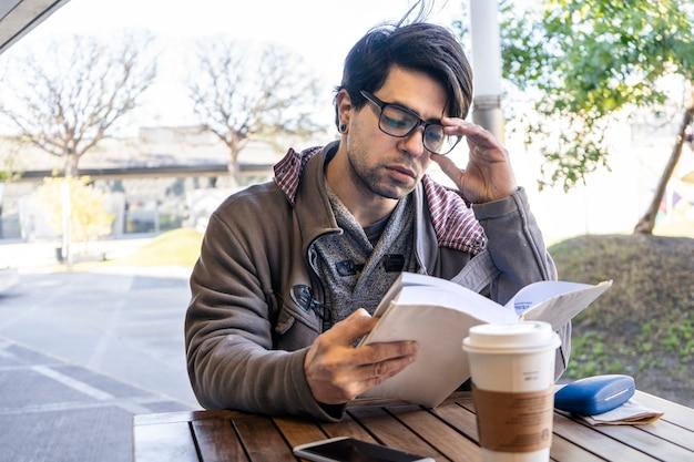 책을 읽으면서 커피를 마시는 바에 앉아 있는 매력적인 남자의 중간 길이 샷.