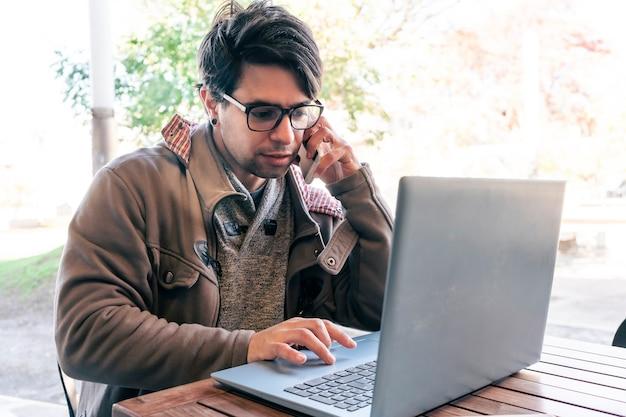 바에 앉아 노트북 작업을 하고 동시에 휴대전화로 통화하는 남자의 중간 길이 샷. 온라인 작업 개념입니다.