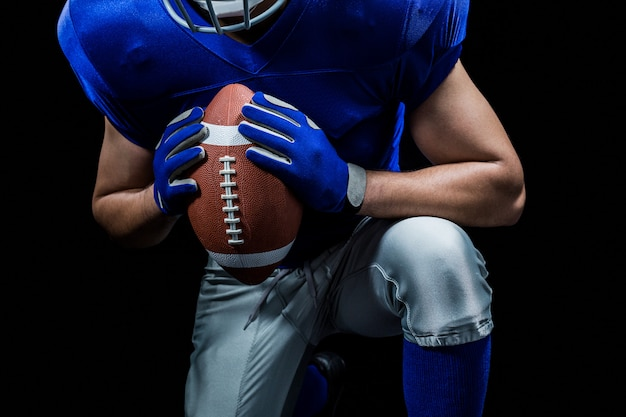 Mid section of american football player kneeling while holding ball