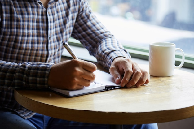 Mid-section of anonymius man in plaid shirt writing notes at the cafe table