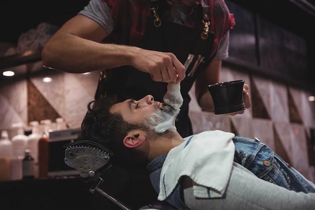 Sezione centrale del barbiere che applica la crema sulla barba dei clienti